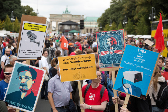"Participants hold placards reading (L to R) ""Team Edward"", ""reintroduction of basic rights"", ""yes we scan"" and ""1984 was not supposed to be an instruction manual"" during a demonstration against governmental surveillance on August 30, 2014 in Berlin. (AFP/DPA)"