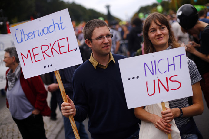 "People hold placards during a ""Freiheit Statt Angst"" (Freedom instead of Fear) protest calling for the protection of digital data privacy and the reigning in of digital surveillance practices, in Berlin August 30, 2014. The placards read, ""Put Merkel under surveillance..."", ""...Not us."" (Reuters/Thomas Peter)"