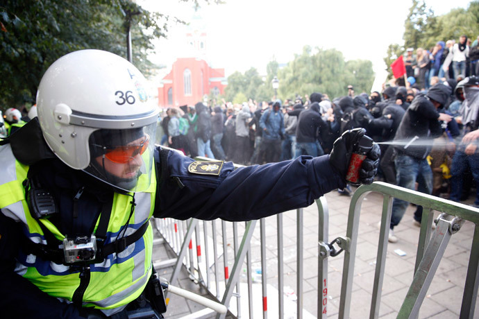 A police officer uses a spray during clashes with demonstrators protesting against an election meeting organised by right-wing political group The Party of the Swedes (Svenskarnas Parti), at the Kungstradgarden square in central Stockholm August 30, 2014. (Reuters / Fredrik Persson)