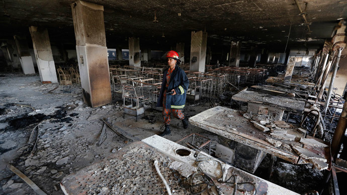 A firefighter inspects the Standard Group garment factory which was on fire in Gazipur November 29, 2013.(Reuters / Andrew Biraj)