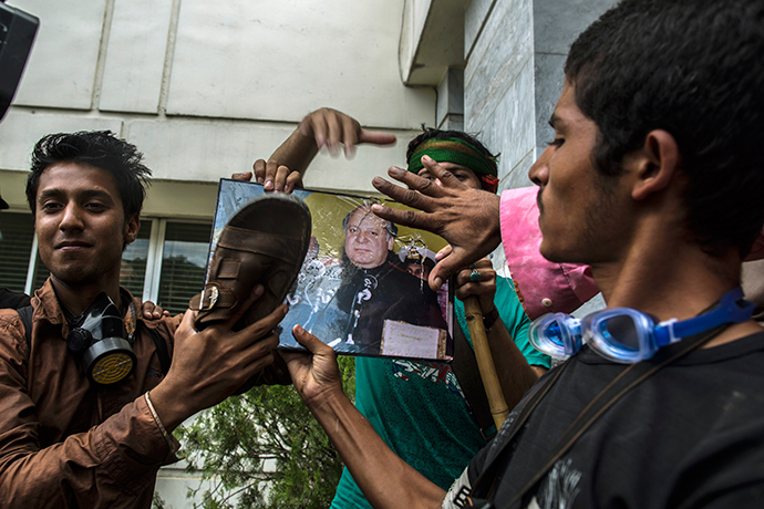 Supporters of Tahir ul-Qadri, a Sufi cleric and leader of Pakistan Awami Tehreek (PAT) party, use a sandal to hit a portrait of Prime Minister Nawaz Sharif, as a sign of disrespect, after storming the building of the state television channel PTV, during the Revolution March in Islamabad September 1, 2014 (Reuters / Zohra Bensemra)