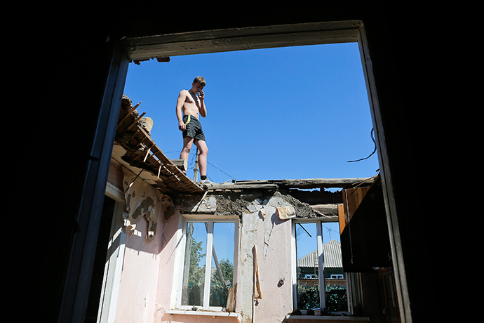 A man stands at the top of a house destroyed during the recent shelling in the eastern Ukrainian town of Ilovaysk, August 31, 2014 (Reuters / Maxim Shemetov)