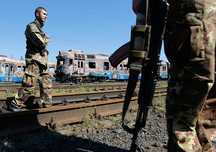 Anti-goverment fighters stand in front of destroyed trains at a railway station in the eastern Ukrainian town of Ilovaysk August 31, 2014 (Reuters / Maxim Shemetov)