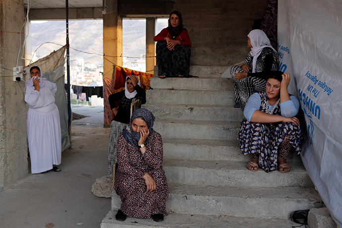 Displaced people from the minority Yazidi sect who fled the violence in the Iraqi town of Sinjar, wait for aid at an abandoned building that they are using as their main residence, outside the city of Dohuk (Reuters / Youssef Boudlal)