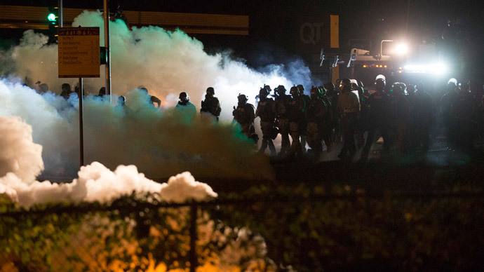 Riot police clear a street with smoke bombs while clashing with demonstrators in Ferguson, Missouri August 13, 2014.(Reuters / Mario Anzuoni)