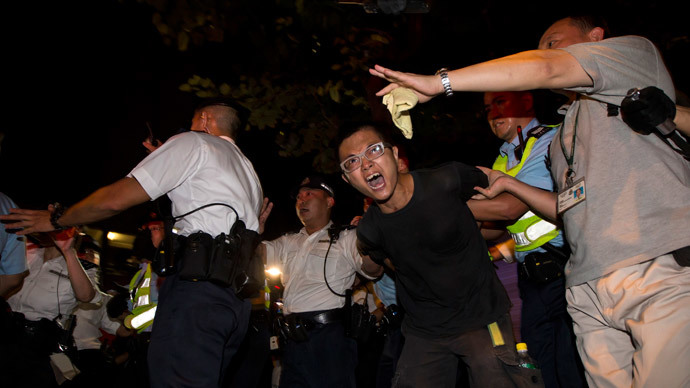 A pro-democracy activist is detained by the police during a confrontation outside the hotel where China's National People's Congress (NPC) Standing Committee Deputy General Secretary Li Fei is staying, in Hong Kong September 1, 2014.(Reuters / Tyrone Siu )