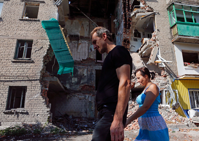 People walk past a building damaged by shelling in Snizhne (Snezhnoye), Donetsk region, August 29, 2014.(Reuters / Maxim Shemetov)