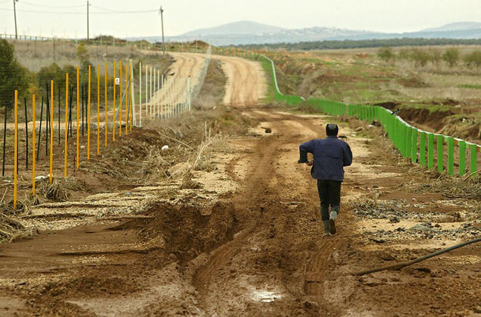 File photo. A Palestinian man, who works in Israel, walks back home as he crosses the green line separating the Jenin area in the north of the West Bank from the Israeli part at the agricultural village of Ram-On. (AFP Photo / Sven Nackstrand)