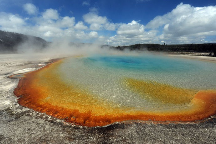 View of the 'Sunset Lake' hot spring with it's unique colors caused by brown, orange and yellow algae-like bacteria called Thermophiles, that thrive in the cooling water turning the vivid aqua-blues to a murkier greenish brown, in the Yellowstone National Park, Wyoming. (AFP Photo / Mark Ralston)