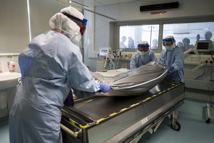 Medical personnel, wearing protective gear, take part in a drill with a dummy to demonstrate the procedures of transporting an Ebola victim, in Hong Kong September 2, 2014. (Reuters/Tyrone Siu)