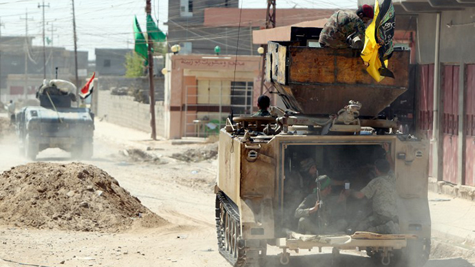 Iraqi Shiite militia fighters ride in an armoured personnel carrier (APC) after pushing back Islamic State (IS) militants on September 3, 2014, on the road between Amerli and Tikrit. (AFP Photo / Ahmad Al-Rubaye)