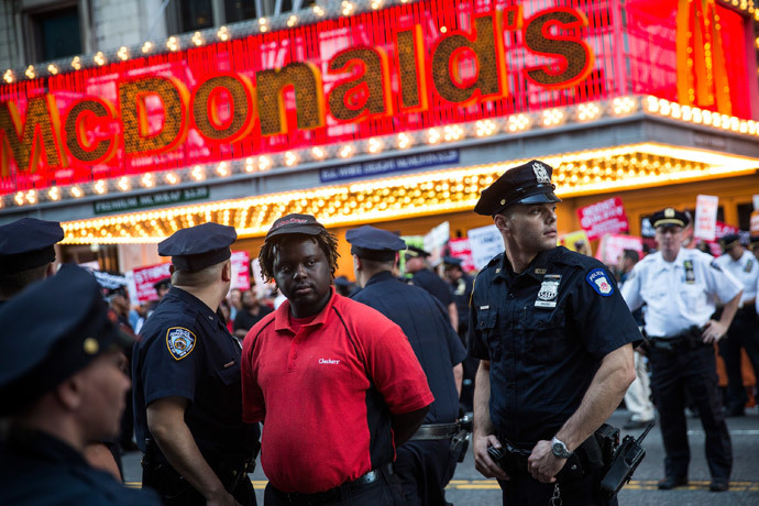 A protester demanding higher wages and unionization for fast food workers is arrested by police near Times Square on September 4, 2014 in New York City. (AFP Photo / Andrew Burton)