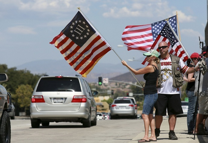 Anti-immigration protesters wave flags at motorists in Murrieta, California on July 19, 2014 (Reuters/Sandy Huffaker)