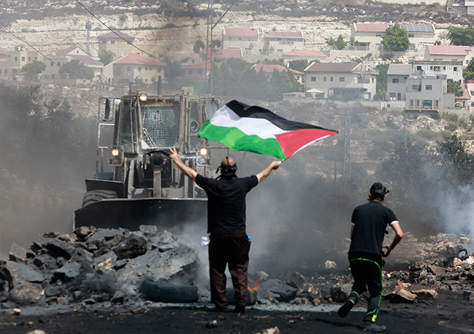 A protester holds a Palestinian flag in front of an Israeli army bulldozer during clashes following a protest against the nearby Jewish settlement of Qadomem, seen in the background, in the West Bank village of Kofr Qadom near Nablus September 5, 2014 (Reuters / Abed Omar Qusini)