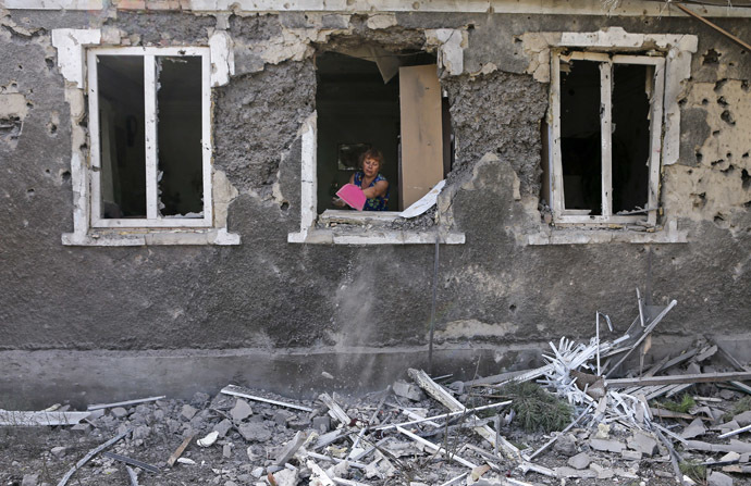 A woman cleans debris from her house damaged by what locals say, was recent shelling by Ukrainian forces in Donetsk August 23, 2014. (Reuters/Maxim Shemetov)