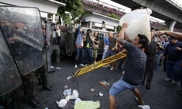 A protester against military rule throws a plastic garbage bin at soldiers during a scuffle at Victory Monument in Bangkok May 28, 2014. (Reuters)