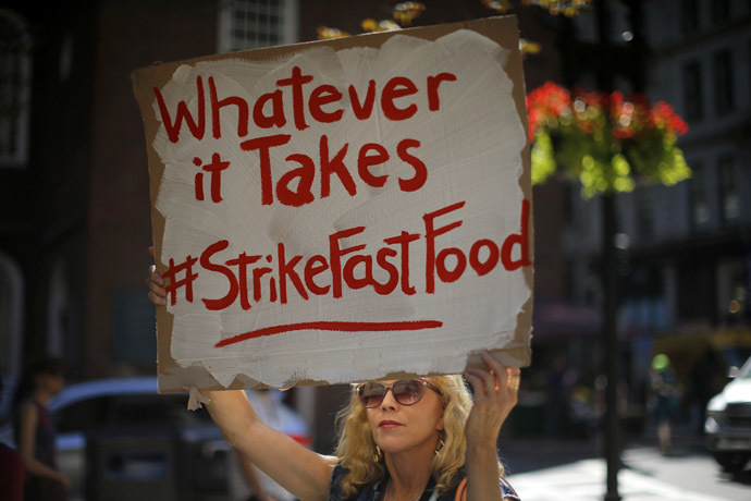 "A woman holds a sign reading ""Whatever it Takes"" during a protest for higher wages in Boston, Massachusetts September 4, 2014. (Reuters/Brian Snyder)"
