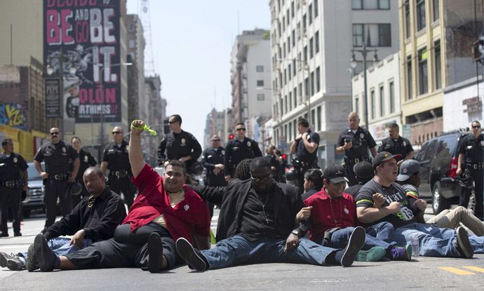 Activists sit in the street during a protest demanding better wages for fast-food workers in Los Angeles, California September 4, 2014. (Reuters/Mario Anzuoni)
