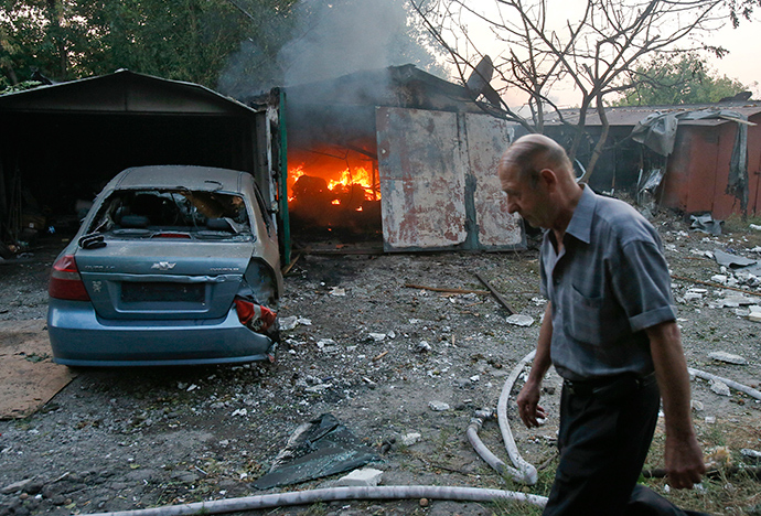 A man walks past a garage set ablaze by what locals say was shelling by Ukrainian forces in Donetsk, September 4, 2014 (Reuters / Maxim Shemetov)