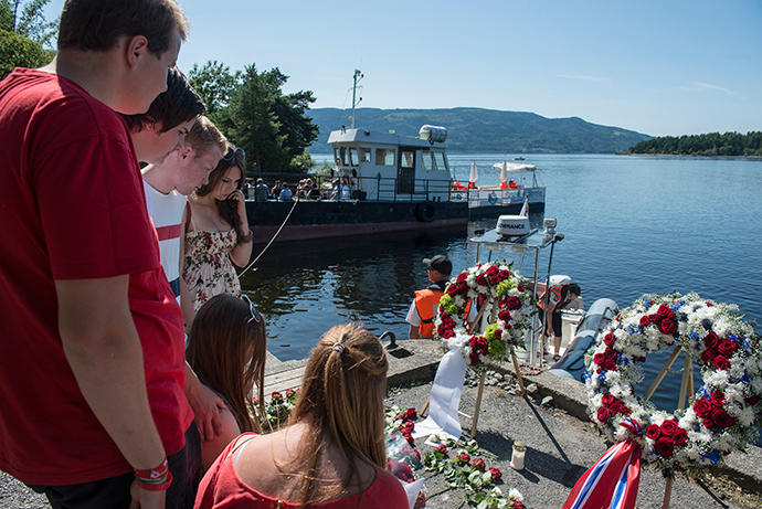 Members of AUF, the Labour Party Youth Organization, attend a wreath laying ceremony to mark the second year anniversary of the twin Oslo-Utoya massacre by self confessed killer Anders Breivik in Utvika July 22, 2013 (Reuters / Aleksander Andersen)