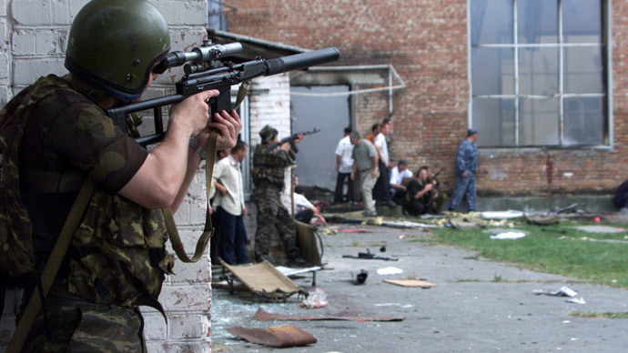 Russian special forces troops take cover while soldiers stormed a school building seized by heavily armed masked men and women in the town of Beslan in the province of North Ossetia near Chechnya, September 3, 2004. (Reuters / S.Dal GD)