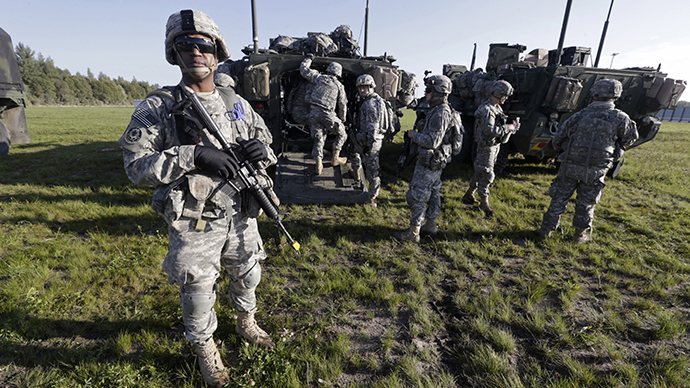 """U.S. second cavalry regiment soldiers stand with armoured personal carriers during the """"Steadfast Javelin II"""" military exercise in the Lielvarde air base, September 6, 2014. (Reuters / Ints Kalnins)"""