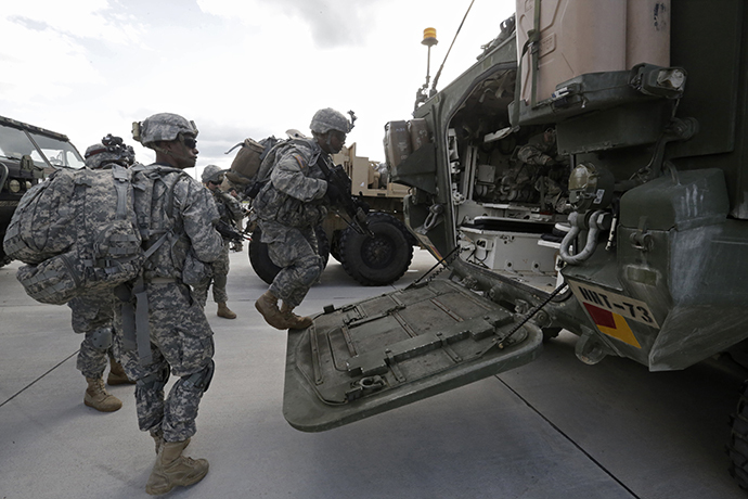 """U.S.173 airborne brigade soldiers climb onto armoured personal carrier """"Stryker"""" during the """"Steadfast Javelin II"""" military exercise in the Lielvarde air base, September 6, 2014. (Reuters / Ints Kalnins)"""