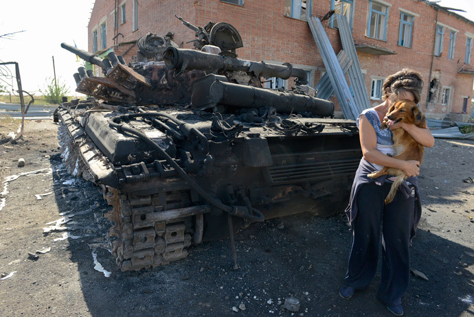 A woman holds a dog beside a destroyed tank in the courtyard of the local kindergarten in the village of Talakovka, some 22 kilometres northeast of Mariupol, on September 6, 2014.(AFP Photo / Alexander Khudoteply)