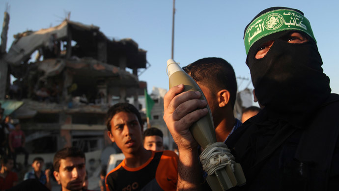 A Hamas militant displays a mortar shell as he celebrates what the militants say was a victory over Israel, in front of a destroyed house in the Shejaia neighborhood east of Gaza City August 27, 2014.(Reuters / Majdi Fathi)
