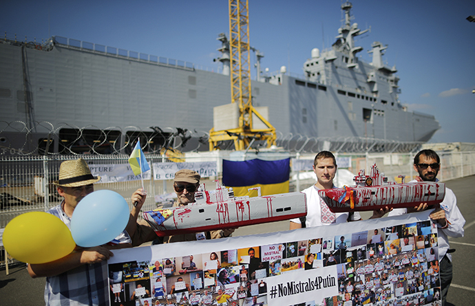 People hold up models of the Mistral-class helicopter carrier warship during a demonstration against a contract to deliver the warship to Russia, at the STX Les Chantiers de l'Atlantique shipyard site in Saint-Nazaire, September 7, 2014. (Reuters / Stephane Mahe)