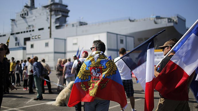 People hold Russian flags, French flags and placards during a demonstration supporting a contract to deliver the Mistral-class helicopter carrier Vladivostok warship to Russia, at the STX Les Chantiers de l'Atlantique shipyard site in Saint-Nazaire, September 7, 2014. (Reuters / Stephane Mahe)