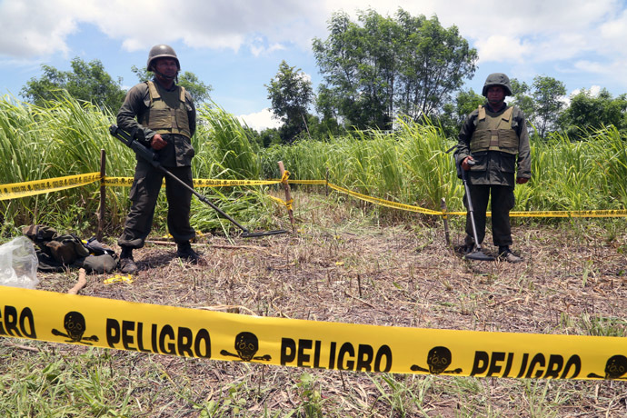 Handout picture released by the Nicaraguan presidency press office showing two Nicaraguan soldiers standing guard in the site where an alleged meteorite struck on September 7, 2014 in Managua. (AFP Photo)