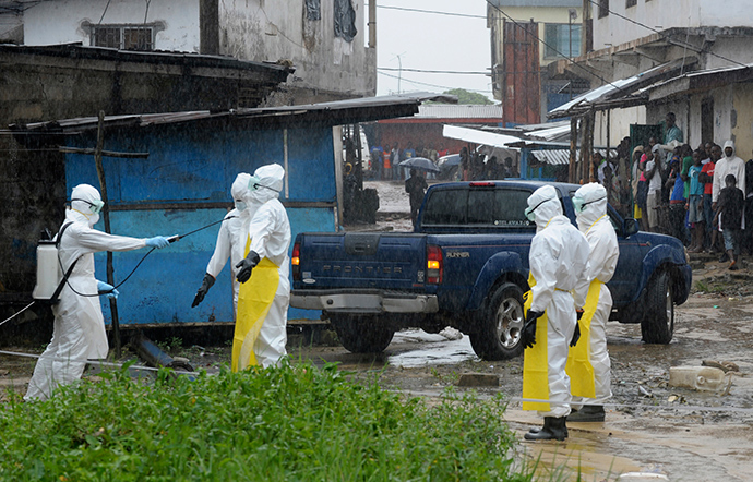 Health workers wearing protective clothing disinfect themselves after an abandoned dead body presenting with Ebola symptoms was found at Duwala market in Monrovia (Reuters / 2Tango)