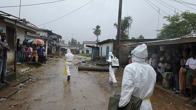 Health workers wearing protective clothing prepare to carry an abandoned dead body presenting with Ebola symptoms at Duwala market in Monrovia (Reuters / 2Tango)