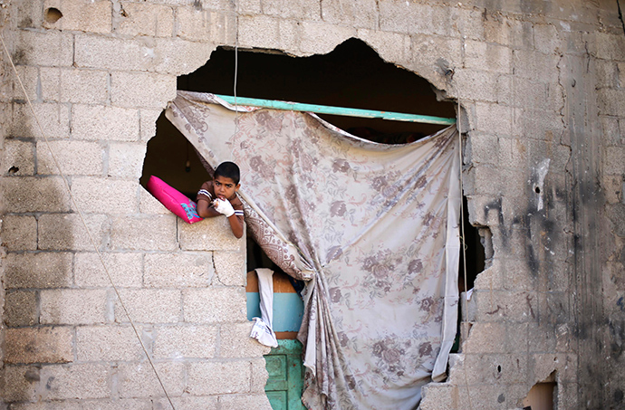 A Palestinian boy looks out of his damaged house after a ceasefire was declared, in the east of Khan Younis in the southern Gaza Strip August 27, 2014 (Reuters / Ibraheem Abu Mustafa)