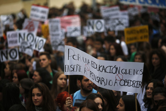 "Students hold a banner that reads, ""For an education that teaches us to think, not to obey"", on the second day of a 48-hour nationwide student strike to protest against rising fees and educational cuts in Madrid March 27, 2014.(Reuters/Susana Vera)"