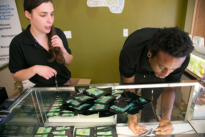 "Employees stock shelves at Cannabis City before their ""high noon"" grand opening during the first day of legal retail marijuana sales in Seattle, Washington July 8, 2014 (Reuters / Jason Redmond)"