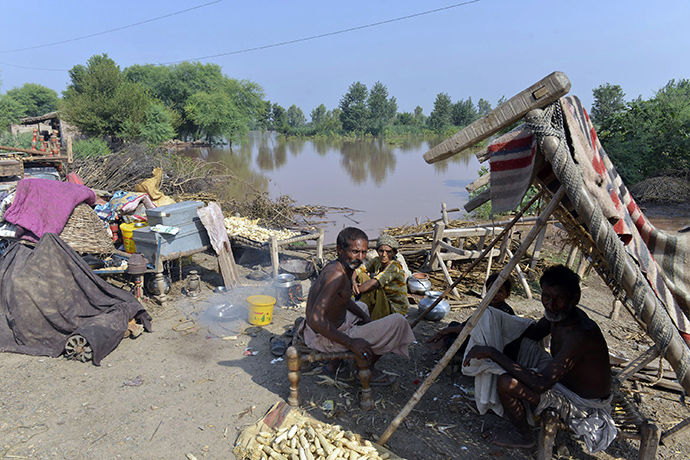 Pakistani residents affected by flooding gather on higher ground with their belongings in Jhang, in the central Punjab province on September 9, 2014 (AFP Photo / Arif Ali)