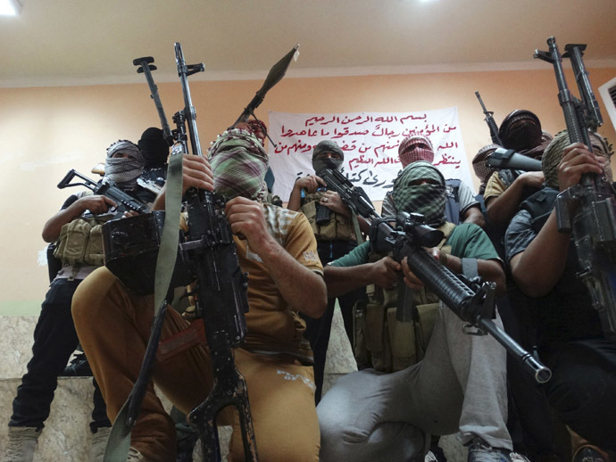 Tribal fighters carrying their weapons pose for photographs during an intensive security deployment to fight against militants of the Islamic State, formerly known as the Islamic State of Iraq and the Levant (ISIL), in the town of Haditha, northwest of Baghdad August 25, 2014. (Reuters/Osama Al-dulaimi)