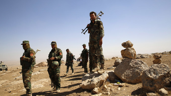Kurdish Peshmerga fighters carry their weapons in an area overlooking Baretle village (not pictured) September 8, 2014. (Reuters/Ahmed Jadallah)