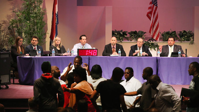 Mayor James Knowles (seated R) ) and city council members wait until angry residents are calmed down during the Ferguson city council meeting on September 9, 2014 in Ferguson, Missouri. (AFP Photo/Scott Olson)