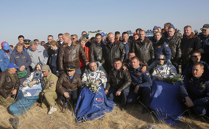 Russian search and rescue team members pose for a photo with Russian cosmonauts Oleg Artemyev (front-2nd L), Alexander Skvortsov (C) and US NASA astronaut Steven Swanson (front 2nd R) after the landing of the Soyuz TMA-12M spacecraft near the Kazakhstan city of Zhezkazgan on September 11, 2014. (AFP Photo / Maxim Shipenkov)