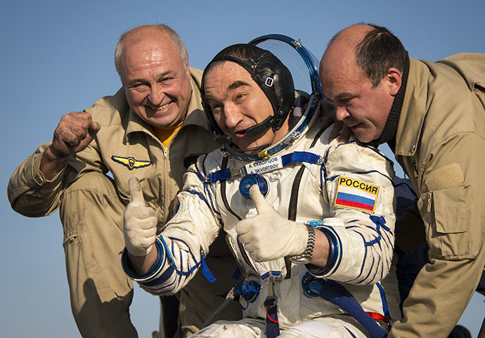 Expedition 40 Flight Engineer Alexander Skvortsov of the Russian Federal Space Agency (Roscosmos) gives a thumbs up as he is helped out of the Soyuz Capsule just minutes after he and Flight Engineer Oleg Artemyev of Roscosmos, and Expedition 40 Commander Steve Swanson of NASA, landed in their Soyuz TMA-12M capsule in a remote area near the town of Zhezkazgan, Kazakhstan on Thursday, Sept. 11, 2014. (AFP Photo / Bill Ingalls)