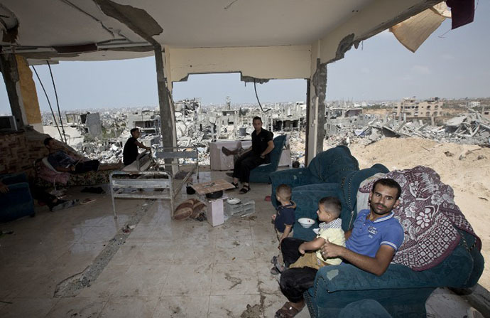 Palestinians sit inside their destroyed house after returning home in the Tufah neighbourhood in eastern Gaza City on August 31, 2014. (AFP Photo / Mahmud Hams)
