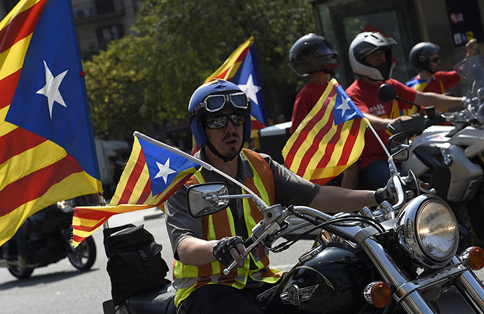 A biker with an independentist flag rides through Barcelona during Catalonia National Day (Diada) on September 11, 2014. (AFP Photo / Lluis Gene)