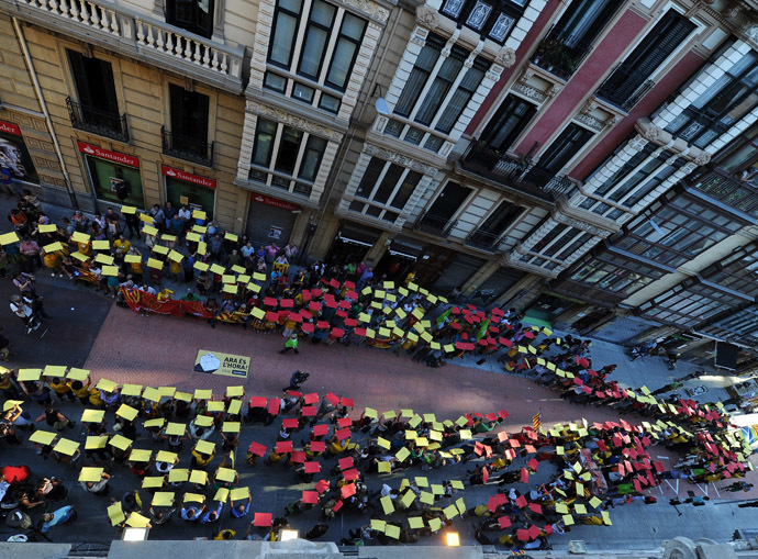People hold placards with the colours of the Catalan flag as they take part in a demonstration in support of a Catalan vote on independence from Spain, in the northern Spanish Basque city of Bilbao on September 9, 2014, ahead of the Diada. (AFP Photo/Rafa Rivas)