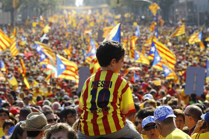 A boy wearing Lionel Messi's jersey sits on the shoulders of a relative as Catalans holding independentist flags (Estelada) gather on Gran Via de les Corts Catalanes during celebrations of Catalonia National Day (Diada) in Barcelona on September 11, 2014. (AFP Photo/Quique Garcia)