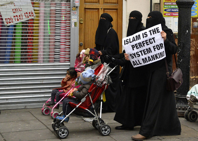 Women hold placards during a march and rally in east London December 13, 2013. (Reuters/Toby Melville)