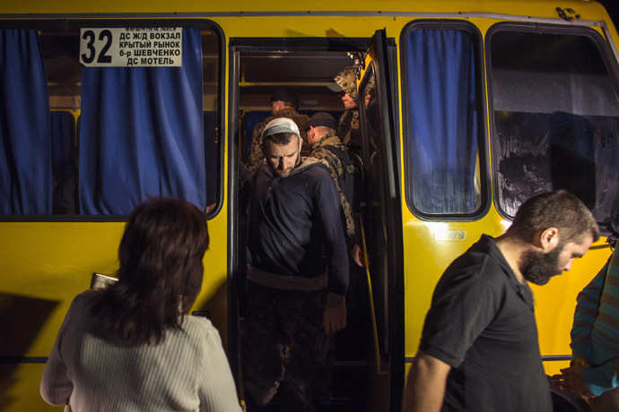 Members of the Ukrainian government forces, who are prisoners-of-war (POWs), exit a bus as they wait to be exchanged, north of Donetsk, eastern Ukraine, September 12, 2014. (Reuters/Marko Djuric)