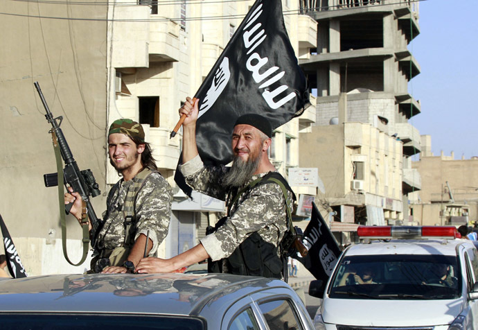 Militant Islamist fighters wave flags as they take part in a military parade along the streets of Syria's northern Raqqa province. (Reuters)